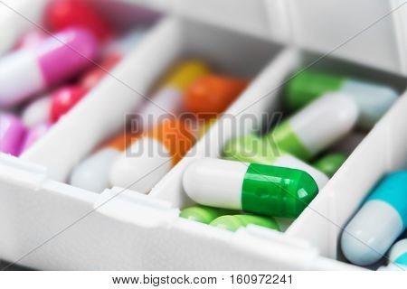 container with various pills in different colors. Focus on a green pill