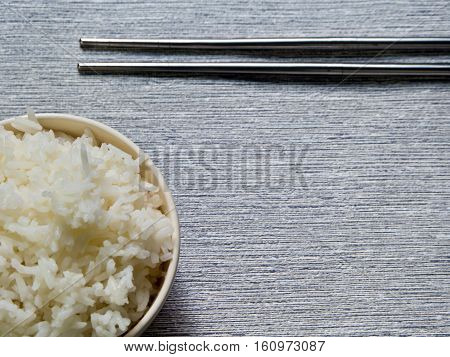 Rice in a cup and metal chopsticks on gray background