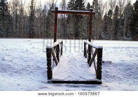 wooden bridge across the ravine in the woods under a layer of snow