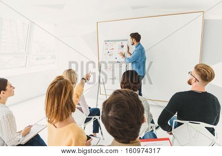 What is this. Serious guy is standing at blackboard and hardly elucidating information. Group asking questions