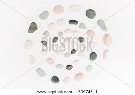 Creative spiral arrangement of colored stones. Mint pink beige and grey stones on white. Flat lay top view