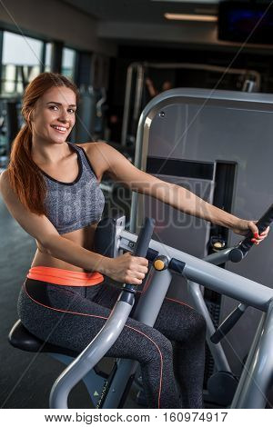 Muscular young brunette doing exercises on the simulator in the gym. She is wearing a gray tracksuit. Woman looking at the camera