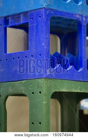 Green and blue Plastic bottle Crates stacked in piles at the liquour store stock.