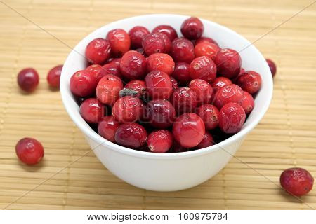 Cranberries in a round white bowl and scattered berries on brown straw mat top view