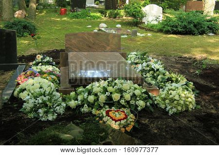 Various sympathy or funeral flowers on a grave