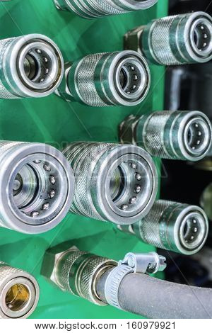 Several hydraulic coupling connector on a green panel.