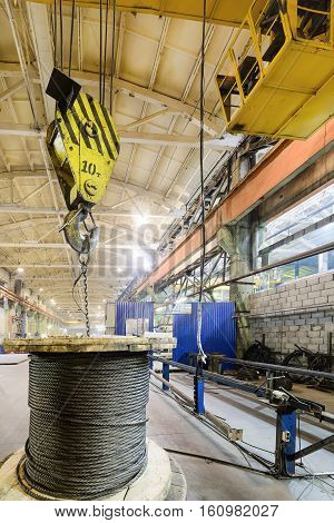 The bridge crane lifts a coil with a steel rope. Industrial background.