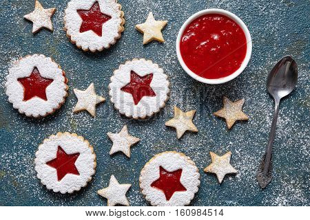 Cookie stars. Assorted cookies. Homemade biscuits cookies with strawberry jam. Home Useful pastries. Flat lay. Traditional Austrian Linzer cookie on green background. Top view.