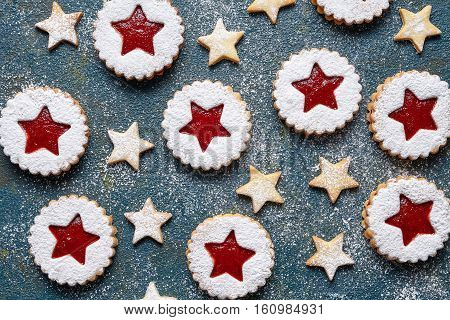 Assorted cookies. Christmas festive homemade ginger cookies star with strawberry jam. Flat lay. Traditional Austrian Linzer cookie on green background. Top view.