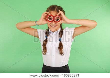 Beautiful school girl holding two insulating tape on eyes for radiant look on green