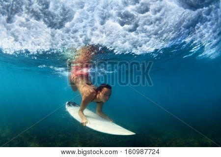 Sportive girl in bikini in action. Surfer with surf board dive underwater under breaking ocean wave. Healthy lifestyle. Water sport swim extreme surfing in adventure camp on summer beach vacation