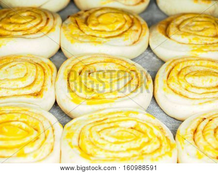 Closeup Of Raw Cinnamon Buns After Proofing With Egg Yolk, On Baking Paper