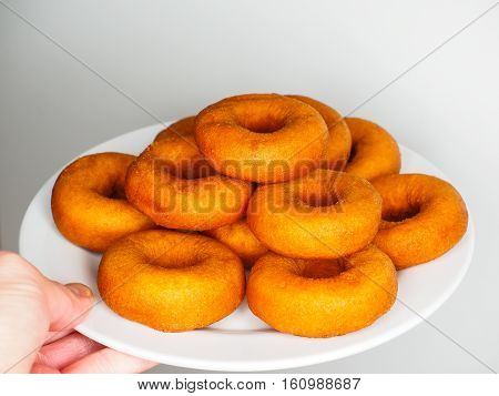 Male Person Holding A Plate Of Freshly Made Dark Brown Doughnuts