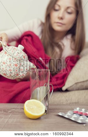 Sick woman lying in bed with high fever and a flu pouring some tea from a teapot in a glass. Lemon and pills on the table focus on the teapot