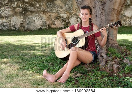 Pretty hispanic teenage girl playing an acoustic guitar sitting on the grass