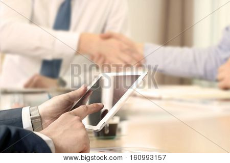 Business partners handshaking over business objects on workplace. businessman working with digital tablet