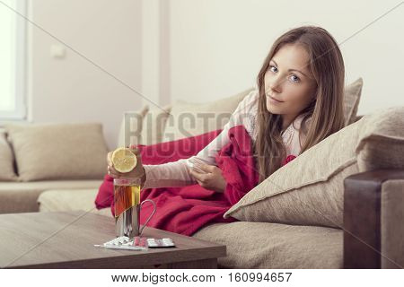 Sick woman lying in bed with high fever and a flu squeezing a lemon juice in her tea.