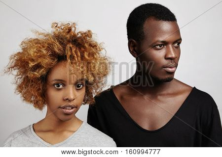 Two Beautiful Young African People Standing Against White Studio Wall. Handsome Man In Trendy V-neck