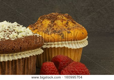 Photo close up two muffins sponge and cocoa sprinkled with grated chocolate and fresh raspberries an old stone kitchen table. Horizontal view from side