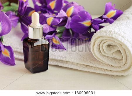 Flower essence dropper bottle,violet Iris, white terry towel wrap.Floral decorated spa set. Warm toned.