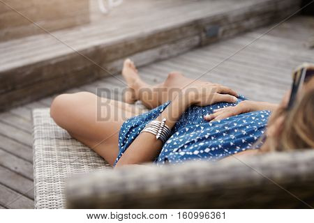 Rear View Of Woman Expecting Baby Lying On Sunlounger, Spending Holidays At Health Resort. Young Pre