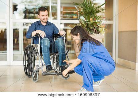 Nurse Helping Patient In A Wheelchair