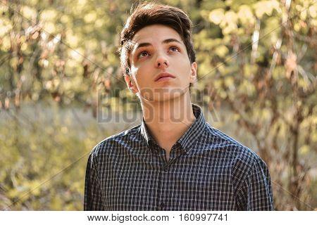 Pensive faithful teenage boy looking up hoping