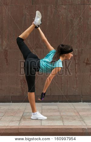 Female athlete warming up by stretching her legs outdoors. Sporty young woman doing yoga standing split exercise on the city street.