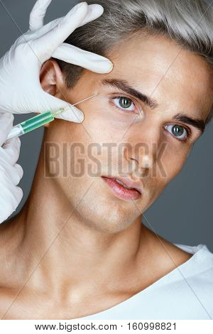 Attractive man receiving beauty injection in the area around the eyes. Doctor makes cosmetic injection. Beauty treatment.