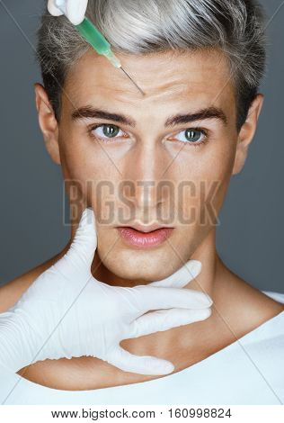 Beautiful man face and beautician hands with syringe. Doctor makes cosmetic injection in forehead. Beauty concept