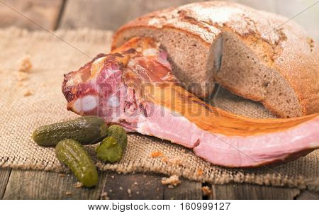 Products on an old wooden table rural style. On a napkin from a sacking bread ham on edges cucumbers lies.