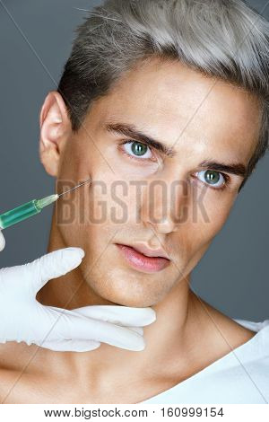 Attractive man getting beauty injection in cheekbones. Injections of skin rejuvenation. Cosmetic procedures