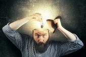 A new idea concept. Image bearded man twists a light bulb in his head as a metaphor of a new idea. Eureka! poster