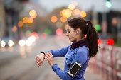 Beautiful young woman in the city with smart phone, smartwatch and earphones, listening music. Using a fitness app for tracking weight loss progress, running goal or summary of her run. Rear view. poster