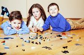 funny cute children playing lego at home, boys and girl smiling, first education role lifestyle close up poster