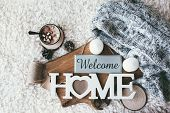 Winter homely scene, scandinavian style. Warm knit sweater, candles, cup of sweet cocoa with marshmallows and other decor on tray in bed. Wooden craft letters Welcome Home. Lazy cold weekend. poster