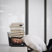 Businessman on laptop with a pile of books on head. Oppressed by work concept poster