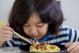 Happy Asian child eating delicious noodle with chopstick