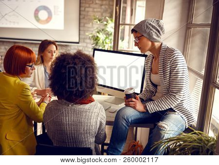 Informal group of females at work together in office