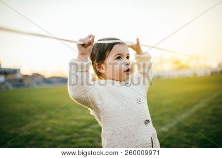 Portrait Of Pretty Girl Toddler Looking Away On Green Grass And Sunset Background. Happy Child In Ou