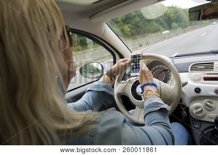 Bottrop, Germany - Aug 16, 2018: A Blond Woman Is Checking Her Smartphone While She Is Driving On A