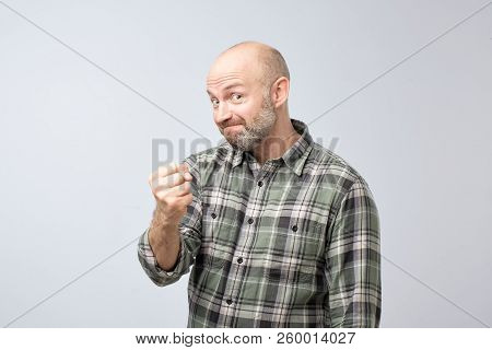 Bearded Mature Man Holding Fist Up Looking At Camera With Threat On Gray Background. He Pretends To