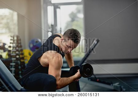 Handsome Sporty Man Flexing Muscles With Barbell In Dark Gym. Sport Concept. Atheletic Muscular Guy