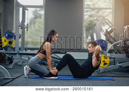 Handsome Man Doing Abdominal Crunches Press Exercise On Mat With Sports Female Personal Trainer In G
