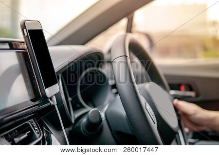 Male Driver Hand Holding On Steering Wheel Using Smartphone For Gps Navigation. Mobile Phone Mountin