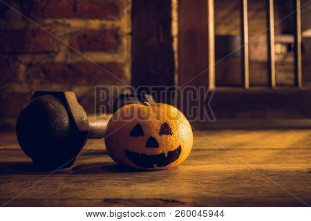 Orange With Head Pumpkins  Haunted Spooky Face  With Black Iron Dumbbell. Halloween Festival With Fi