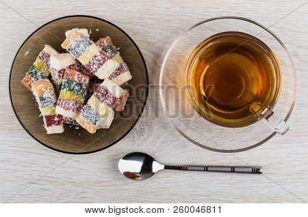 Multicolor Rakhat-lukum In Brown Saucer, Cup Of Tea, Teaspoon On Wooden Table. Top View