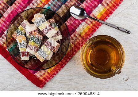 Multicolor Rakhat-lukum In Brown Saucer On Napkin, Cup Of Tea, Teaspoon On Wooden Table. Top View
