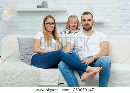 Family portrait. Happy family sitting on couch and having fun at home, smiling. Family with one child.
