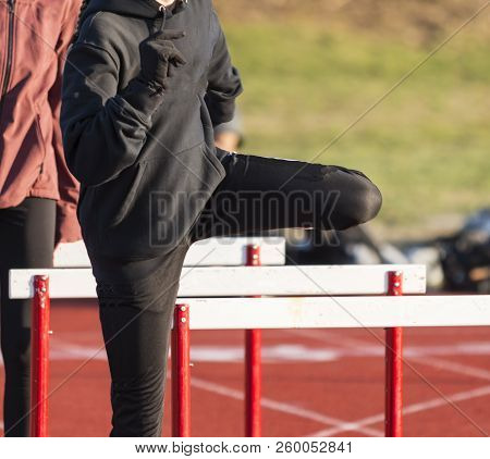 A High School Hurdler Is Covered Up With Sweats And Gloves While Warming Up For A Race On A Cold Day